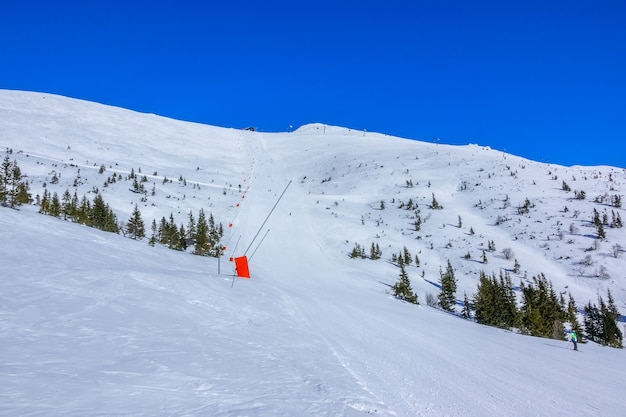 Słoneczna pogoda w ośrodku narciarskim. niebieskie niebo. długa i prosta trasa z armatkami śnieżnymi