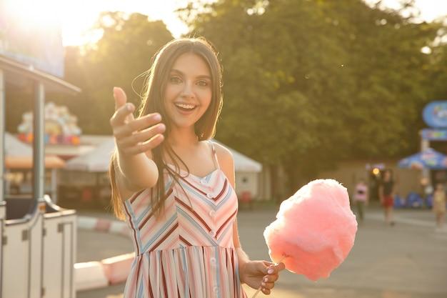 Słoneczna, urocza brunetka o brązowych włosach pozuje nad zielonym parkiem z różową watą cukrową w dłoni, podaje rękę i zaprasza na spacer z nią, uśmiechając się radośnie