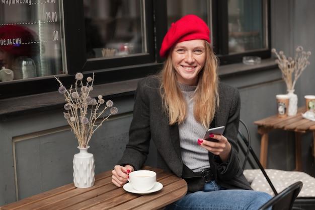 Słoneczne ujęcie pozytywnej młodej ładnej blondynki w eleganckich ubraniach siedzącej przy stole na tarasie i popijającej herbatę, uśmiechającej się szczerze z telefonem komórkowym w dłoni