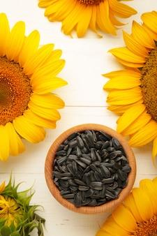 Słonecznik z nasionami w misce na białym tle drewnianych. widok z góry