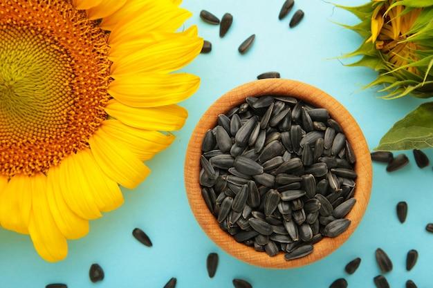 Słonecznik z nasionami w misce na niebieskim tle. widok z góry