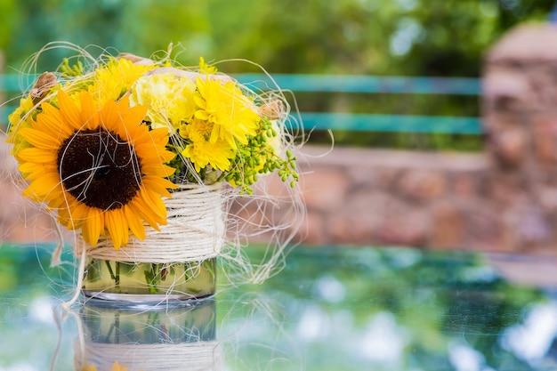 Słonecznikowe i żółte kwiaty w małym wazonie ustawionym na zewnątrz na stole