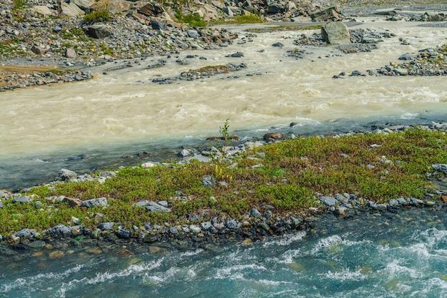 Słoneczny alpejski krajobraz ze zbiegiem dwóch różnych górskich rzek. piękny czysty potok wpada do brudnej rzeki. kolorowa górska sceneria ze zbiegiem dwóch różnych rzek wśród bogatej roślinności.