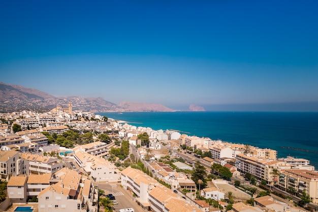 Słoneczny dzień, lato, hiszpański krajobraz wybrzeża morza śródziemnego. plaża z turkusową wodą. turystyczny punkt orientacyjny słońca i plaży w altea, comunidad valenciana, hiszpania