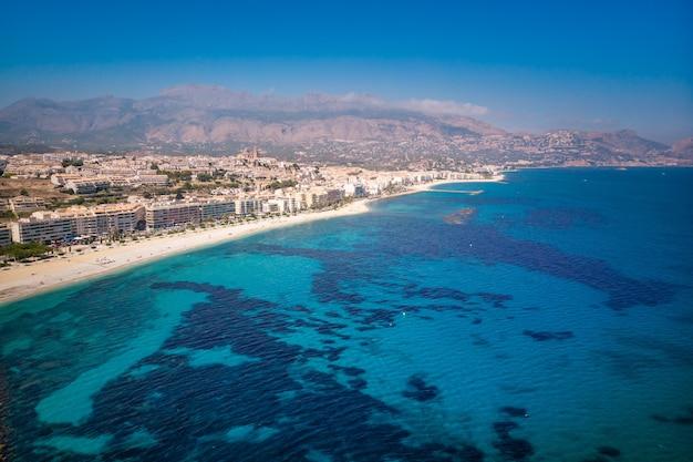 Słoneczny dzień, lato, hiszpański krajobraz wybrzeża morza śródziemnego. plaża z turkusową wodą. turystyczny punkt orientacyjny słońca i plaży w comunidad valenciana, hiszpania