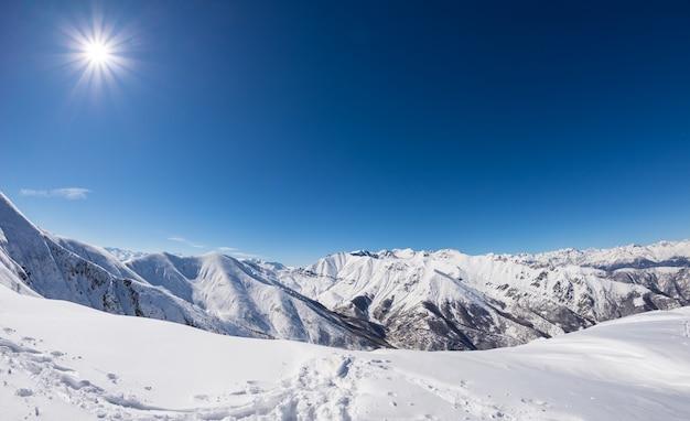 Słoneczny dzień na ośnieżonych pasmach górskich