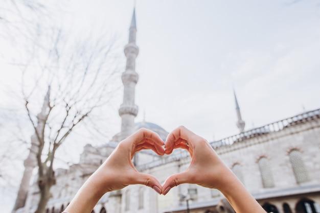 Słoneczny dzień z niebieskim niebem. stambuł, turcja. meczet sułtana ahmeta w słoneczny dzień. piękna kobieta robi kształtowi serce z widokiem meczetu sulejmana wspaniałego w stambule.