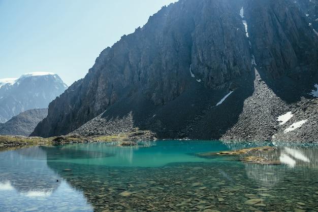 Słoneczny górski krajobraz z lazurowym jeziorem polodowcowym w słońcu. turkusowa czysta woda górskiego jeziora i duża skała. piękne krajobrazy z jeziorem i śniegiem w górach. kamienne dno w przezroczystej wodzie.