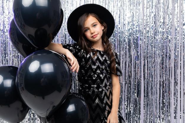 Słoneczny jasny nastolatek dziewczyna na obchody urodzin na tle czarnych balonów helowych i świecidełka.