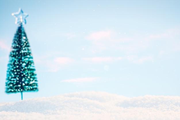 Słoneczny krajobraz ze śniegiem i choinką