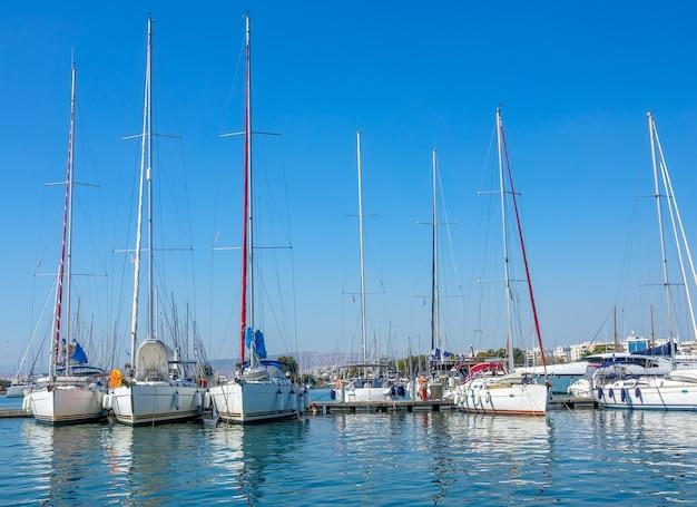 Słoneczny letni dzień. małe greckie miasteczko. wiele jachtów żaglowych w marinie