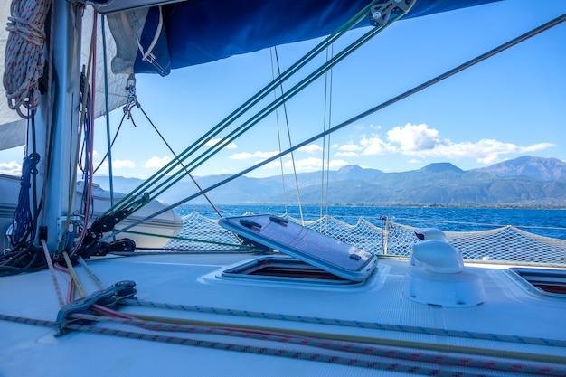 Słoneczny letni dzień na pokładzie jachtu żaglowego. olinowanie i maszt. widok na pagórkowate wybrzeże
