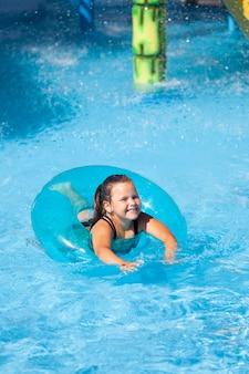 Słoneczny letni dzień w parku wodnym mała szczęśliwa dziewczynka pływa w czystej, błękitnej wodzie basenu w nadmuchiwanym...