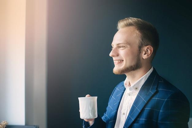 Słoneczny poranek młody biznesmen pije kawę w biurze europejczyk w niebieskiej kurtce