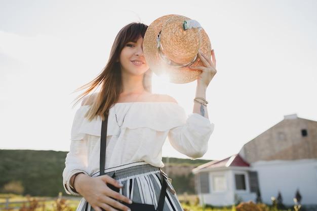 Słoneczny portret uśmiechniętej młodej pięknej stylowej kobiety, trend w modzie wiosna lato, styl boho, słomkowy kapelusz, weekend na wsi, słoneczna, czarna torebka