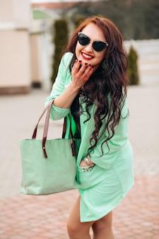 Słoneczny pozytywny portret oszałamiającej kobiety w krótkiej sukience bawiące się na ulicy, radość, szczęście, weekendy, jasne kolory