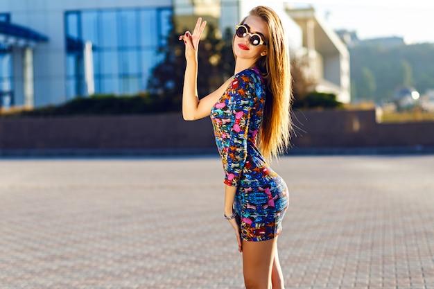 Słoneczny pozytywny portret seksownej, oszałamiającej kobiety w krótkiej sukience, skaczącej i bawiącej się na ulicy, radość, szczęście, weekendy, jasne kolory.