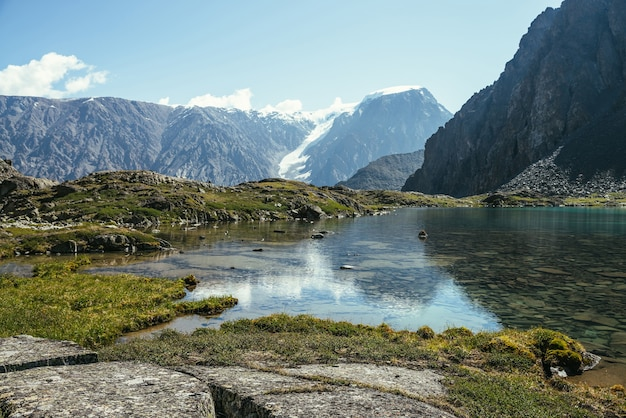 Słoneczny, relaksujący krajobraz z lazurowym jeziorem polodowcowym w słońcu. medytacyjna fala i odbicie lodowca na turkusowej czystej wodzie górskiego jeziora. piękna sceneria z jeziorem i ośnieżonymi górami.