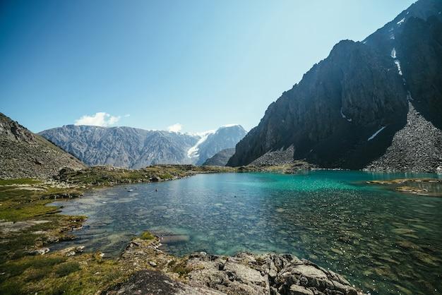 Słoneczny, relaksujący krajobraz z lazurowym jeziorem polodowcowym w słońcu. medytacyjna fala i wiele odbitych świateł na turkusowej powierzchni czystej wody górskiego jeziora. piękna sceneria z jeziorem i lodowcem.