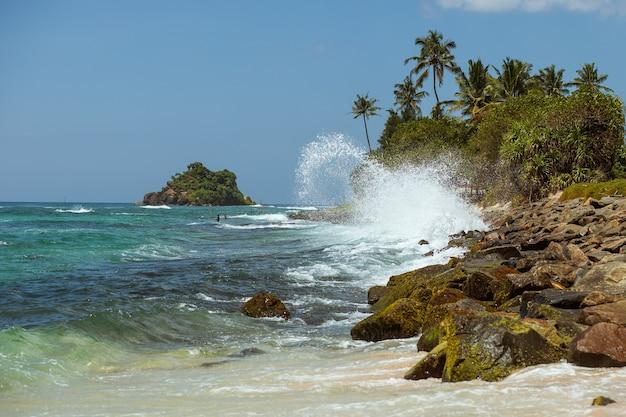 Słoneczny tropikalny skalisty brzeg z falami
