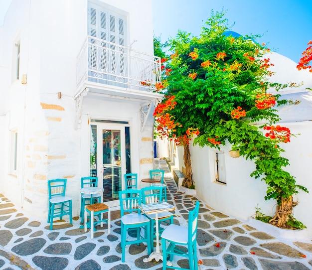 Słoneczny widok na miejsce restauracji i zielone drzewa z białą architekturą greckiej ulicy