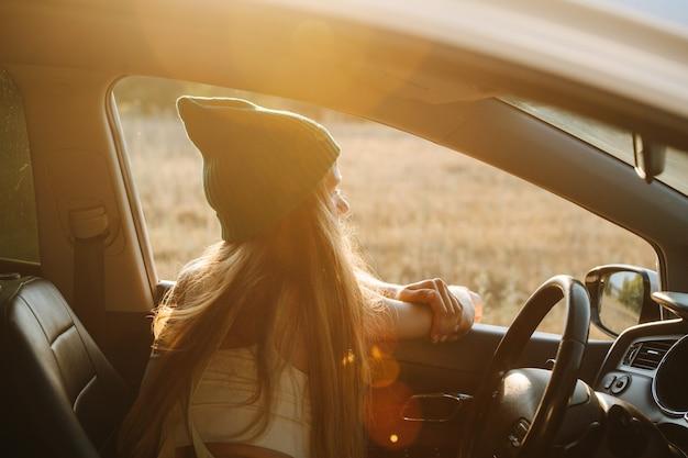 Słoneczny wizerunek kobiety w pomarańczowej czapce zegarka chłodzi w samochodzie, ciesząc się widokami, opierając się o ramę okna. od tyłu.