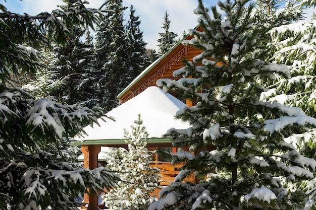 Słoneczny zimowy dzień w lesie. drewniany domek lub domek pokryty śniegiem. ośrodek narciarski i snowboardowy, ferie zimowe na świeżym powietrzu.