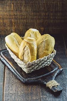 Słony chleb z piekarni brazylijskiej, zwany chlebem francuskim, w koszyku na drewnianym tle