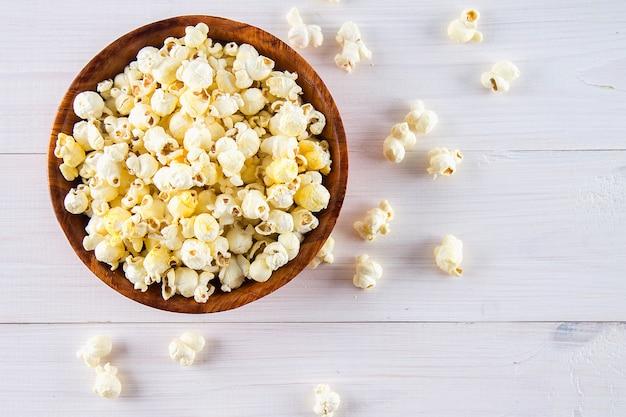 Słony popcorn w drewnianej filiżance jest na białym stole. popcorn leży wokół miski. widok z góry.