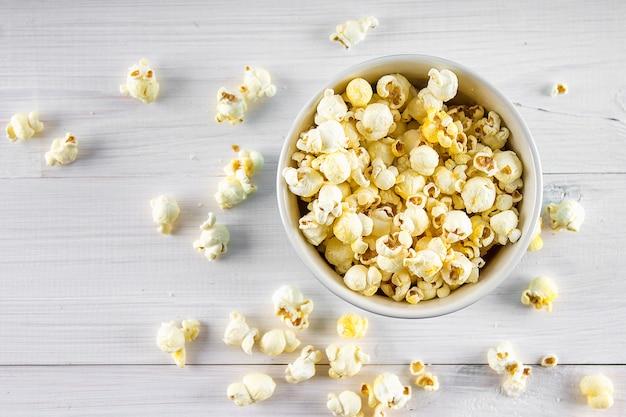 Słony popcorn w niebieskiej filiżance jest na drewnianym stole. popcorn leży wokół miski. widok z góry.