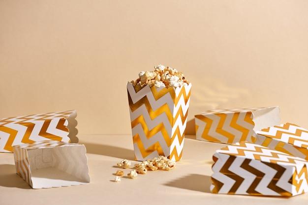 Słony świeży chrupiący domowy popcorn w złotym papierowym kubku na modnej beżowej powierzchni