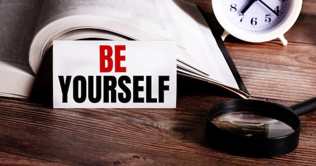 Słowa bądź siebą zapisane na białej karcie obok otwartej książki, budzika i lupy