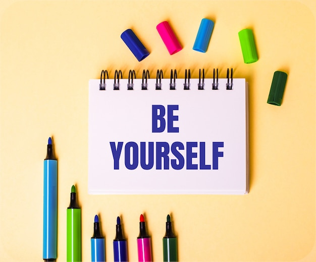 Słowa be yourself zapisane w białym zeszycie na beżowej powierzchni w pobliżu wielokolorowych markerów
