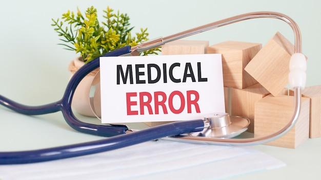 Słowa błędu medycznego napisane na białej karcie medycznej, ze stetoskopem, zielonym kwiatem i drewnianymi klockami.