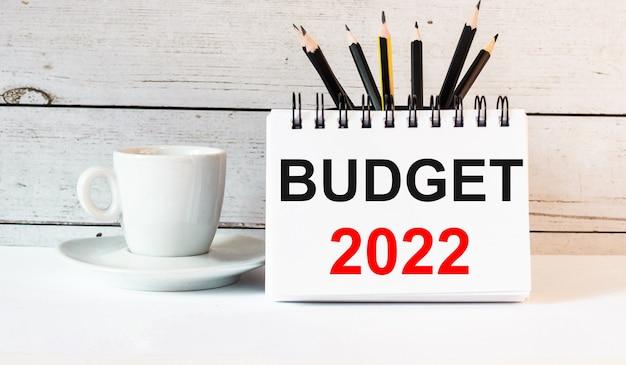 Słowa budżet 2022 są zapisane w białym notatniku obok białej filiżanki kawy na jasnej powierzchni