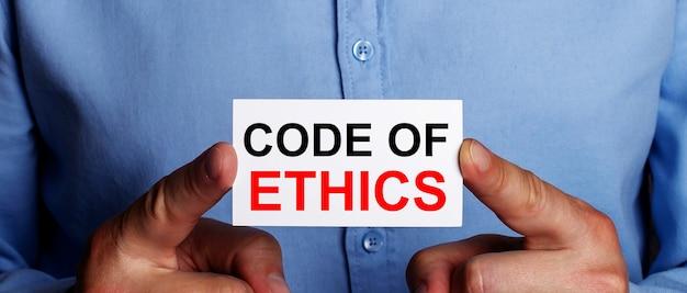 Słowa code og ethics są zapisane na białej wizytówce w dłoniach mężczyzny
