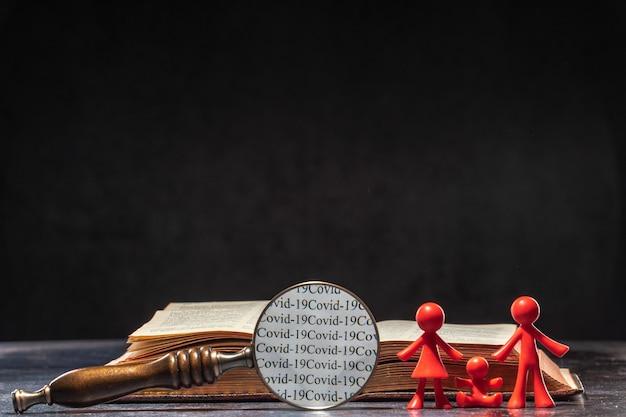 Słowa covida 19 można odczytać przez szkło powiększające. rodzinne postacie stojące obok księgi. pojęcie ludzkości wiedzy o koronawirusie.
