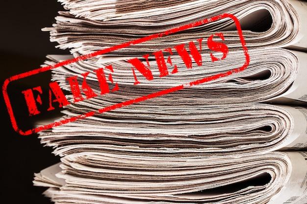 Słowa fake news w czerwonym tekście w gazetach