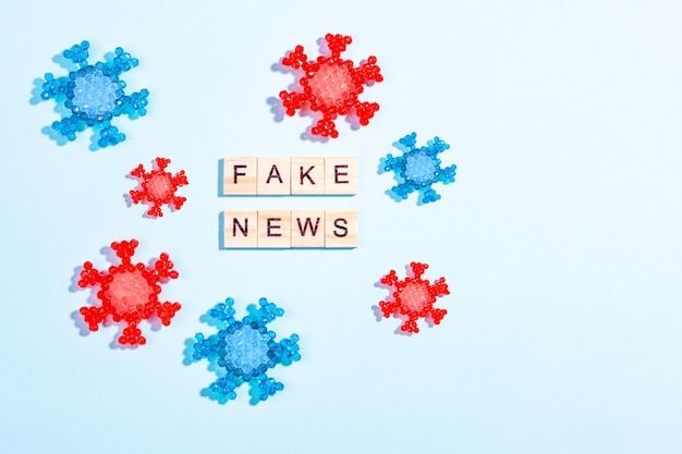 Słowa fałszywe wiadomości wykonane z drewnianych bloków z modelu koronawirusa na niebieskim tle