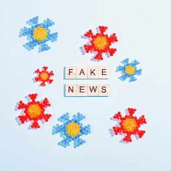 Słowa fałszywe wiadomości wykonane z drewnianych klocków z modelem koronawirusa na bluetable, płasko ułożony, widok z góry. fałszywe wiadomości na temat koncepcji pandemii, dezinformacji w temacie mediów społecznościowych