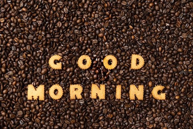Słowa good ranning wykonane z liter herbatników na tle ciemnego ziarna kawy