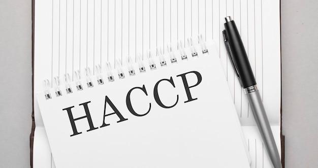 Słowa haccp tekst w notatniku i piórze