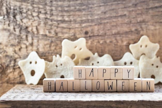Słowa happy halloween na drewnianych kostkach z grupą strasznego ducha na drewnianym tle, jesienny nastrój horror koncepcja halloween z kapeluszem czarownicy nowoczesny design