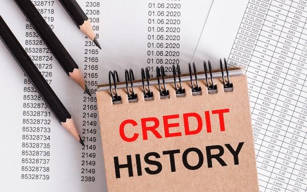 Słowa historia kredytów są zapisane na brązowym notesie