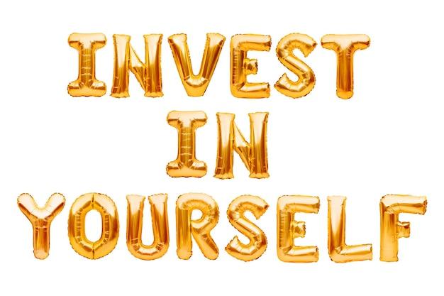 Słowa invest in yourself wykonane ze złotych nadmuchiwanych balonów na białym tle. balony z folii złotej helu tworzące tekst. popraw swoje umiejętności, samorozwój, pomysł na samodoskonalenie.