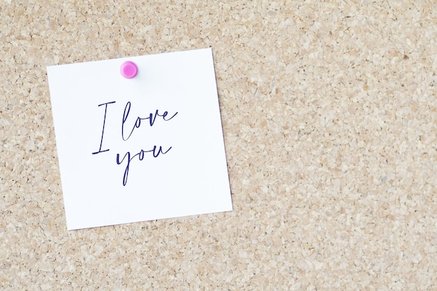"""Słowa """"kocham cię"""" na kartce przypiętej do tablicy za pomocą szpilki"""