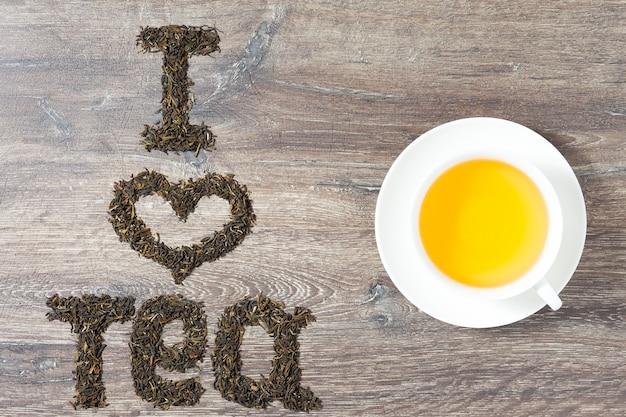 Słowa kocham herbatę z liści zielonej herbaty na tle drewna. tekst po lewej. filiżanka herbaty po prawej