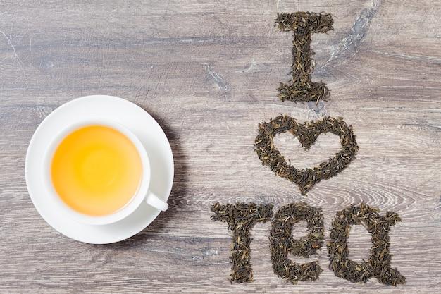 Słowa kocham herbatę z liści zielonej herbaty na tle drewna. tekst po prawej. filiżanka herbaty po lewej