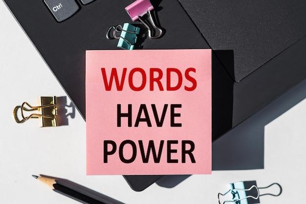 Słowa mają moc napisana jest na papierowej naklejce na klawiaturze laptopa.