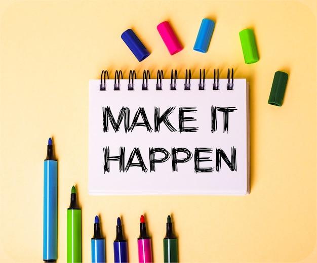 Słowa make it happen zapisane w białym zeszycie na beżowej ścianie w pobliżu różnokolorowych markerów.